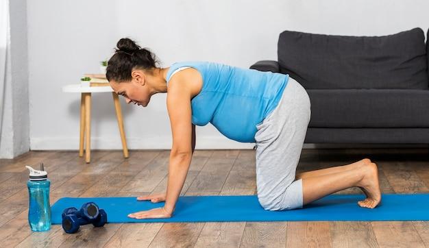 Vista laterale della donna incinta, formazione a casa sulla stuoia con i pesi