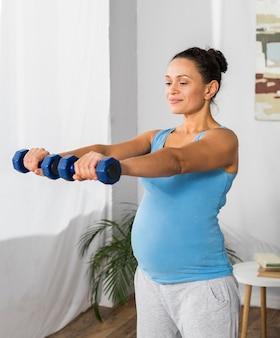 Vista laterale della donna incinta, allenamento con i pesi a casa