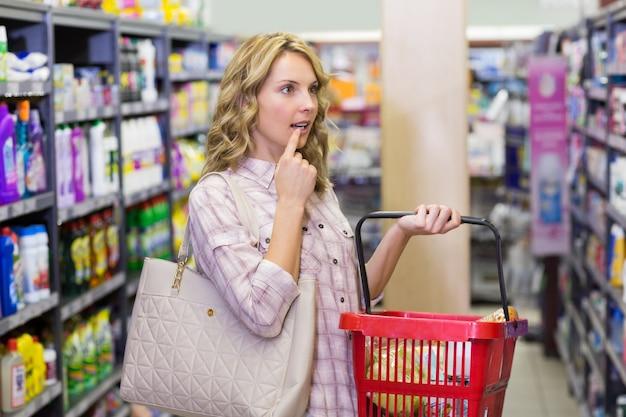 Vista laterale di una bella donna bionda con un sacchetto della spesa e guardando scaffale