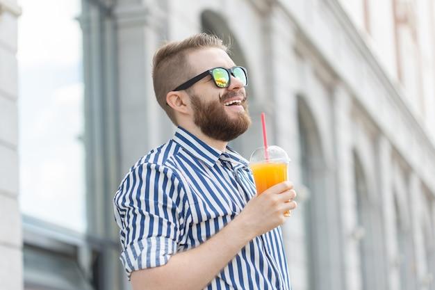 Vista laterale di un giovane uomo d'affari abbastanza allegro con eleganti baffi e barba con succo in mano, passeggiando per la città dopo una giornata lavorativa. concetto di positivo e di riposo.