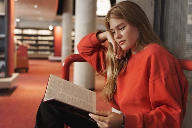 Vista laterale del libro di lettura della ragazza abbastanza intelligente rossa in biblioteca.