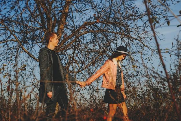 Vista laterale della bella giovane donna e uomo bello sorridente e mano nella mano mentre si cammina nella campagna di autunno insieme.