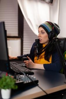 Vista laterale dello streamer pro con le cuffie che giocano a una competizione di giochi sparatutto utilizzando attrezzature moderne. giocatore seduto su una sedia da gioco che utilizza una console wireless e parla con altri giocatori nel microfono.