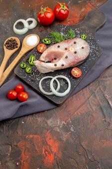 Vista laterale di pesci crudi e pomodori verdi cipolla pepe sul tagliere nero sulle posate asciugamano impostato su una superficie di colore misto Foto Premium