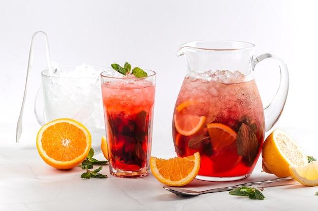 Vista laterale sulla limonata ai frutti rossi in una brocca e vetro isolato