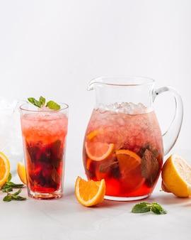 Vista laterale sulla limonata ai frutti di bosco in una brocca e un bicchiere su sfondo bianco