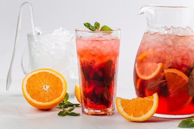 Vista laterale sulla limonata ai frutti rossi in una brocca e un bicchiere
