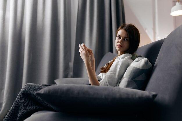 Vista laterale della donna dai capelli rossi con il telefono seduto sul divano