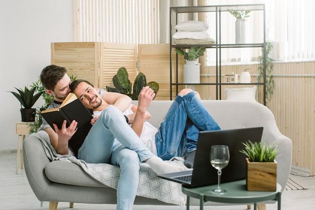 Vista laterale di giovane libro di lettura gay rilassato delle coppie sullo strato a casa