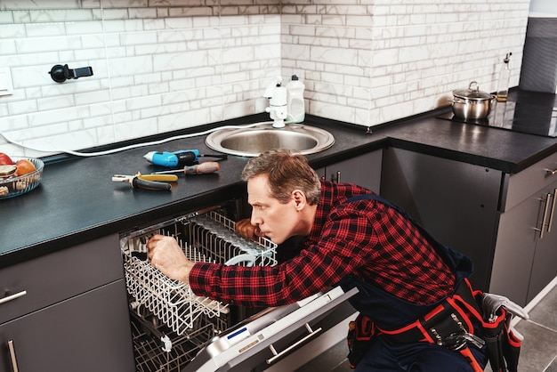 Vista laterale del tecnico maschio di riparazione della lavastoviglie seduto vicino alla lavastoviglie