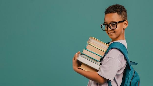Ragazzo di scuola di vista laterale che tiene una pila di libri copia spazio