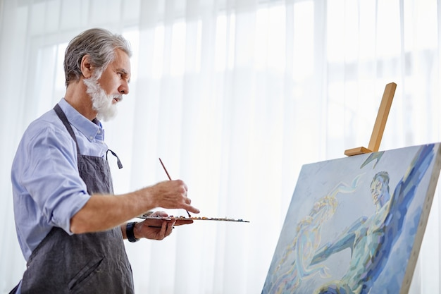 Vista laterale sulla pittura dell'uomo artista dai capelli grigi senior utilizzando la tavolozza del pittore e la tela, a casa, lavora come hobby