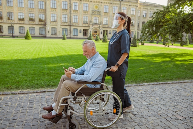 Vista laterale dell'uomo anziano che recupera paziente in sedia a rotelle utilizzando lo smartphone durante una passeggiata con l'infermiera