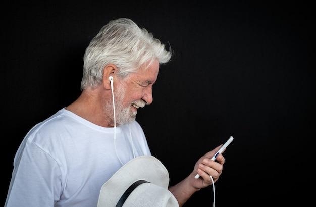Vista laterale di un uomo anziano con barba e cappello bianco che guarda sorridere del telefono cellulare. ritratto di anziani in pensione godendo della tecnologia. sfondo nero