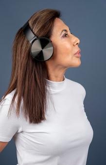 Vista laterale della donna anziana che ascolta la musica con le cuffie