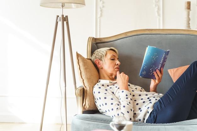 Vista laterale di una signora anziana caucasica dai capelli corti seria sdraiata su un divano a casa