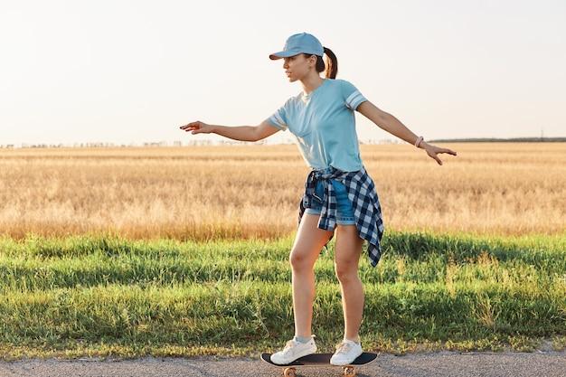 Vista laterale della donna sportiva esile che indossa una maglietta in stile casual e un berretto con visiera che fa skateboard su strada su strada asfaltata, passatempo attivo felice in estate all'aperto.