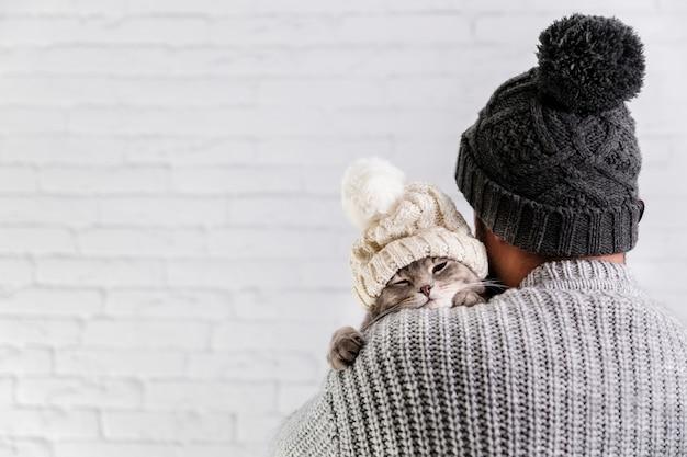 Vista laterale piccolo gattino con cappuccio in pelliccia