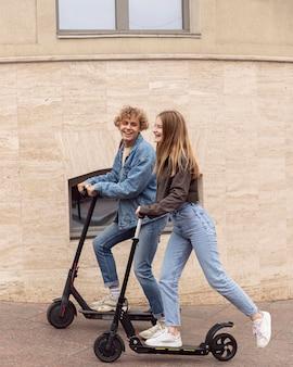 Vista laterale della coppia sorridente utilizzando scooter elettrici in città