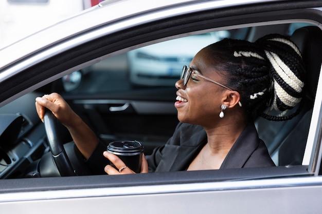 Vista laterale della donna sorridente che mangia caffè all'interno della sua auto