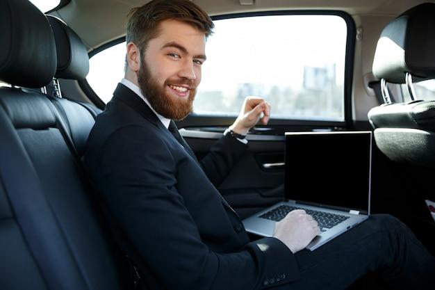 Vista laterale dell'uomo sorridente di affari con il computer portatile