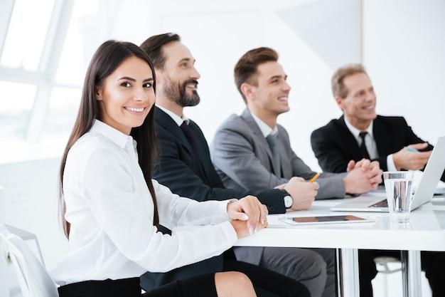 Vista laterale di uomini d'affari sorridenti seduti al tavolo e donna che guarda la telecamera