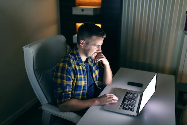 Vista laterale dell'impiegato laborioso sorridente che si siede nell'ufficio a tarda notte