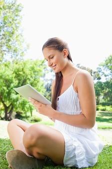 Vista laterale di una donna sorridente utilizzando un tablet pc nel parco