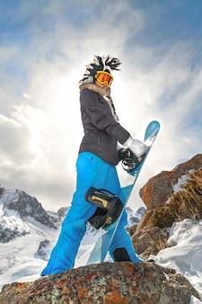 Ritratto dello snowboarder di vista laterale in cappello mohawk divertente in alta montagna della roccia.