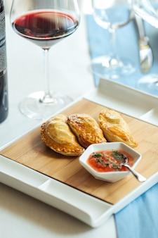 Vista laterale sulle empanadas di torte spagnole con salsa sul tavolo del ristorante