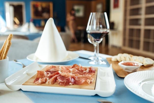 Vista laterale sul jamon di maiale affettato spagnolo sul tavolo servito con vino rosso