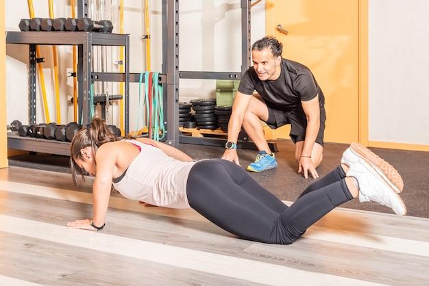 Vista laterale di una sportiva che fa push up con trainer in palestra. concetto di esercizi in palestra.