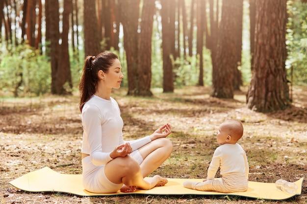 Vista laterale della donna sportiva che fa yoga e meditazione nella foresta con il suo bambino neonato