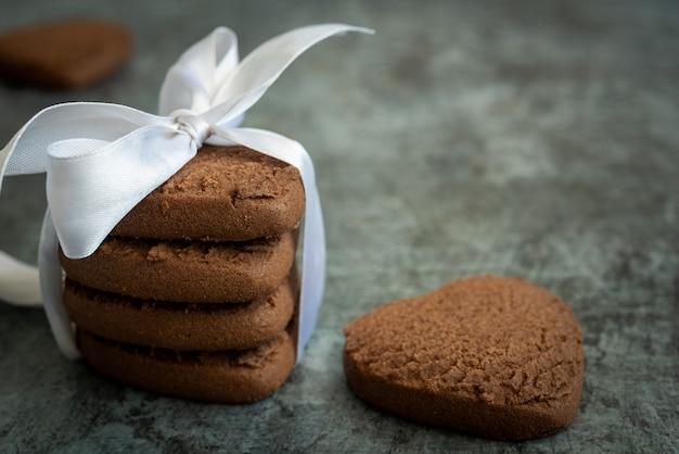 Vista laterale di una pila di biscotti al cioccolato a forma di cuore con un nastro festivo. sfondo festivo