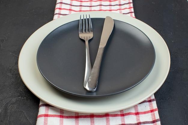 Vista laterale di posate in acciaio inossidabile su colore grigio scuro e piatti vuoti bianchi su asciugamano spogliato rosso su sfondo nero con spazio libero
