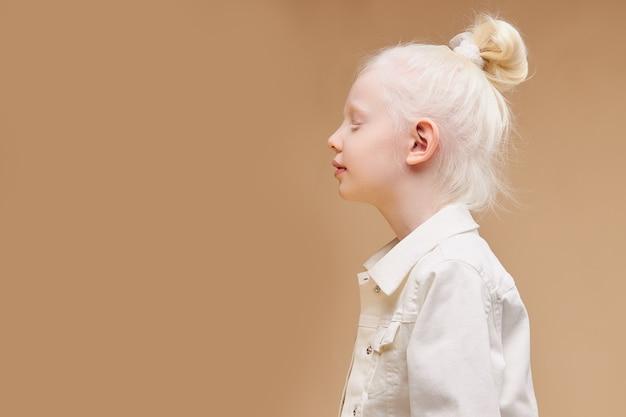 Vista laterale sulla strana bambina caucasica con aspetto insolito