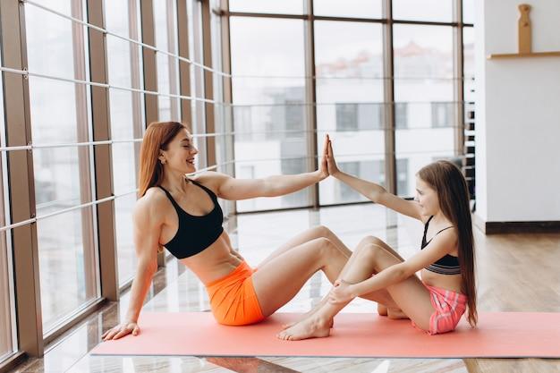 Vista laterale della forte madre e figlia seduta sul tappetino yoga e dando il cinque in palestra