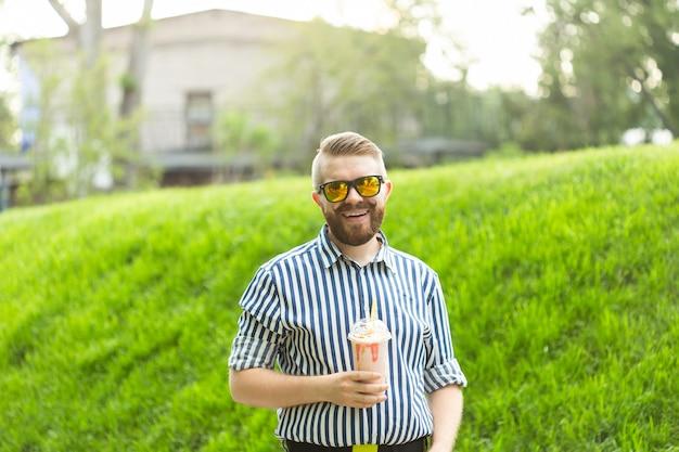 Vista laterale di un giovane alla moda con la barba che tiene un frappè e ammirando la vista sulla città passeggiando nel parco in una calda giornata estiva. il concetto di riposo e relax.
