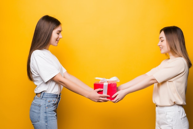 La vista laterale delle giovani donne sorprese tiene la scatola attuale con l'arco del nastro del regalo isolato sulla parete gialla. compleanno della festa della donna, concetto di vacanza.