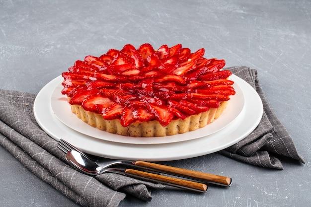 Vista laterale sulla torta con fragole e panna montata sulla superficie grigia
