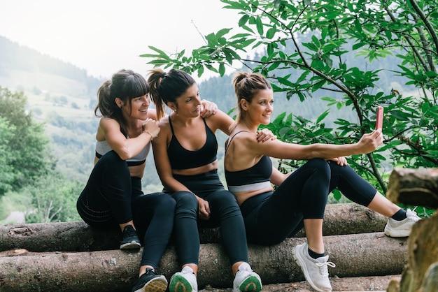 Vista laterale di tre belle donne sportive felici che fanno un selfie video o foto dopo una gara in una foresta verde