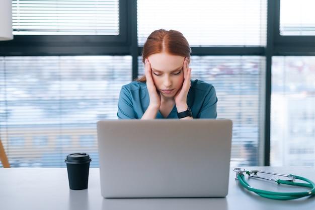 Vista laterale della giovane dottoressa stanca esausta in uniforme medica che ha mal di testa e si sfrega la testa mentre si lavora al computer portatile seduto alla scrivania in ufficio della clinica medica.
