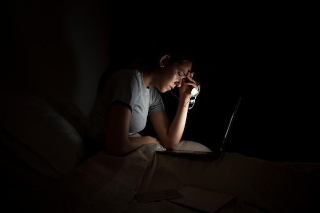 Vista laterale della donna stanca che lavora tardi a casa