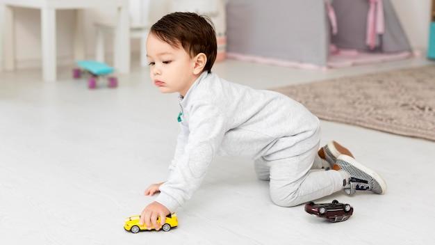 Vista laterale del bambino che gioca con l'automobile del giocattolo