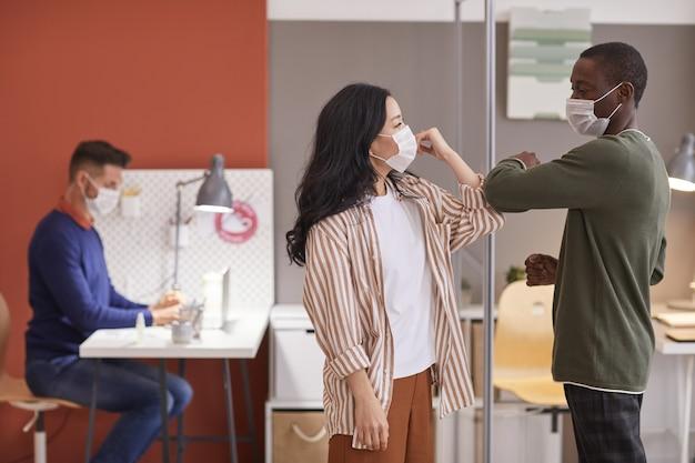 Vista laterale a due colleghi che indossano maschere e gomiti urtando come saluto senza contatto in ufficio, copia dello spazio