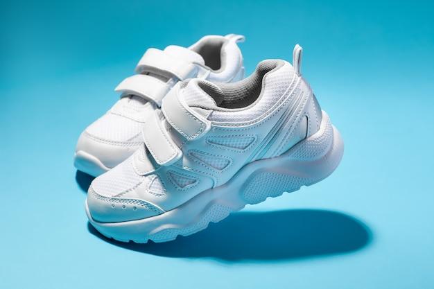 Vista laterale di due sneakers da donna bianche che camminano simulate con chiusure in velcro isolate su uno sfondo blu...