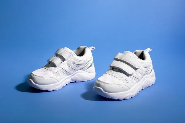 Vista laterale di due scarpe da ginnastica bianche per bambini con chiusure in velcro su uno sfondo di carta viola con...