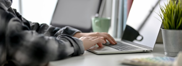 Vista laterale dello studente universitario che prepara il suo prossimo esame con laptop, libri e caffè