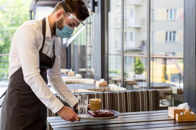 Cameriere di vista laterale con maschera che serve