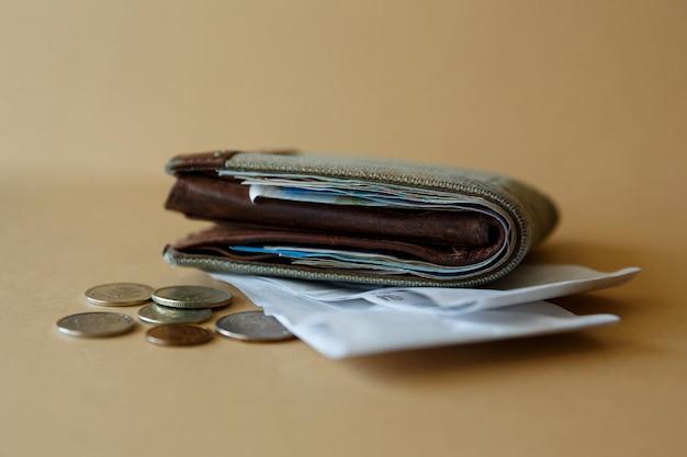 Vista laterale del portafoglio con monete in denaro e assegno circolare dal negozio costi degli acquisti e pagamento dei servizi